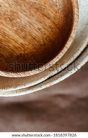 Macro abstract photography of modern minimalist ceramics set and wooden bowl.