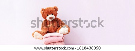 Brown stuffed teddy bear sitting on stack of clean cotton towels or clothes. Childhood care, clothing and plush toy for children in orphanage. Doll for nursery or charity. Website banner, web page Royalty-Free Stock Photo #1818438050