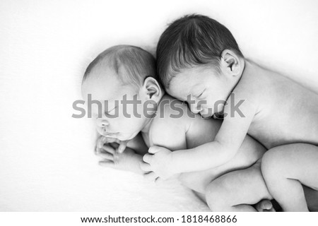 Newborn twins sleeping together in a hug. Babies lies together on blanket. Sibling love from birth - sisters, brothers. Baby care. Black and white picture
