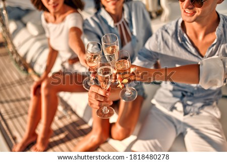 Cheers! Cropped image of group of friends relaxing on luxury yacht and drinking champagne. Having fun together while sailing in the sea. Traveling and yachting concept. Royalty-Free Stock Photo #1818480278