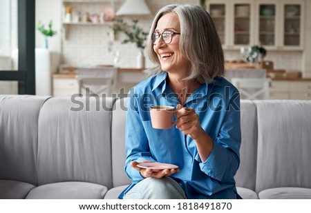 Happy beautiful relaxed mature older adult grey-haired woman drinking coffee relaxing on sofa at home. Smiling stylish middle aged 60s lady enjoying resting sitting on couch in modern living room. Royalty-Free Stock Photo #1818491870