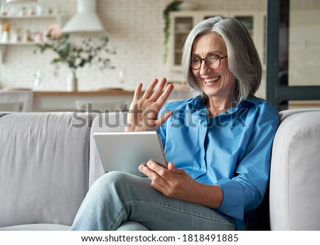 Happy 60s older mature middle aged adult woman waving hand holding digital tablet computer video conference calling by social distance virtual family online chat meeting sitting on couch at home. Royalty-Free Stock Photo #1818491885