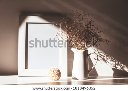 Blank picture frame and Gypsophila flowers in light with shadows, mock up. Still life