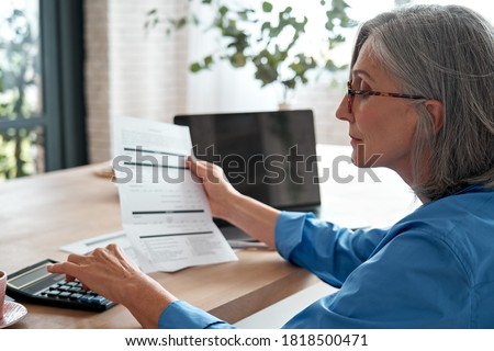 Senior mature business woman holding paper bill using calculator, old lady managing account finances, calculating money budget tax, planning banking loan debt pension payment sit at home office table. Royalty-Free Stock Photo #1818500471