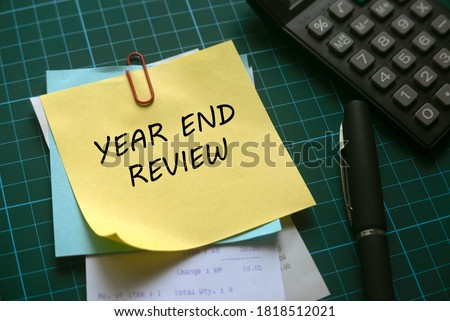 Selective focus of calculator,pen and a stack of memo notes written with Year End Review on a green square background. Royalty-Free Stock Photo #1818512021