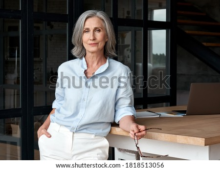 Confident stylish european mature middle aged woman standing at workplace. Stylish older senior businesswoman, 60s gray-haired lady executive leader manager looking at camera in office, portrait. #1818513056