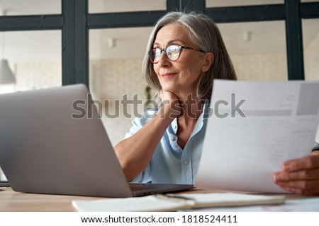 Smiling mature middle aged business woman using laptop working on computer sitting at desk. Happy old businesswoman hr holding cv interviewing distance applicant, senior seeker searching job online. #1818524411