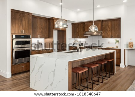 Kitchen in new luxury home with quartz waterfall island, hardwood floors, dark wood cabinets, and stainless steel appliances. Royalty-Free Stock Photo #1818540647