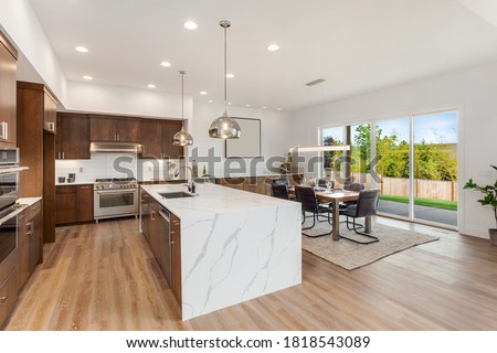 Kitchen in new luxury home with quartz waterfall island, hardwood floors, dark wood cabinets, and stainless steel appliances. Shows view of dining area with large table and place settings. Royalty-Free Stock Photo #1818543089