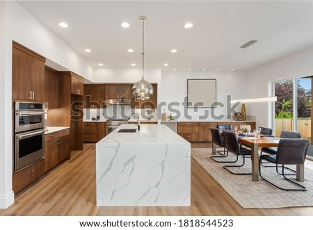 Kitchen in new luxury home with quartz waterfall island, hardwood floors, dark wood cabinets, and stainless steel appliances. Shows view of dining area with large table and place settings. Royalty-Free Stock Photo #1818544523