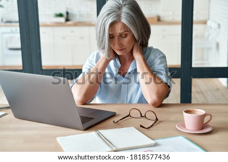 Tired stressed old mature business woman suffering from neckpain working from home office sitting at table. Overworked senior middle aged lady massaging neck feeling hurt pain from incorrect posture. #1818577436