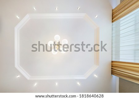 suspended ceiling with halogen spots lamps and drywall construction in empty room in apartment or house. Stretch ceiling white and complex shape. #1818640628