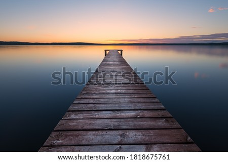 Old wooden pier at sunset. Long exposure, linear perspective Royalty-Free Stock Photo #1818675761
