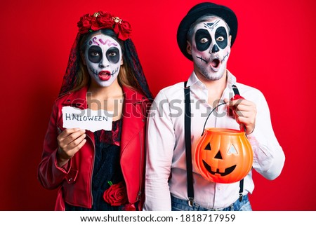 Couple wearing day of the dead costume holding pumpking and halloween paper in shock face, looking skeptical and sarcastic, surprised with open mouth  #1818717959