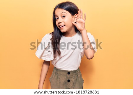 Beautiful child girl wearing casual clothes smiling with hand over ear listening and hearing to rumor or gossip. deafness concept.  #1818728681