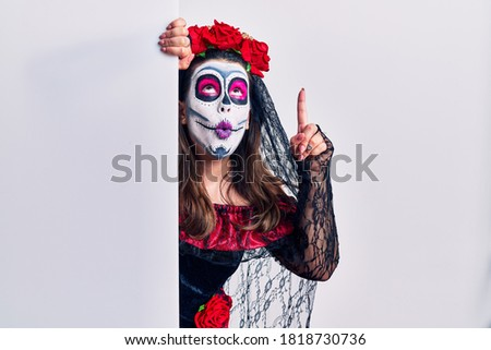 Young woman wearing day of the dead custome holding blank empty banner amazed and surprised looking up and pointing with fingers and raised arms.