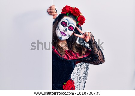 Young woman wearing day of the dead custome holding blank empty banner doing peace symbol with fingers over face, smiling cheerful showing victory