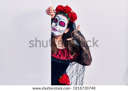 Young woman wearing day of the dead custome holding blank empty banner smiling doing phone gesture with hand and fingers like talking on the telephone. communicating concepts.