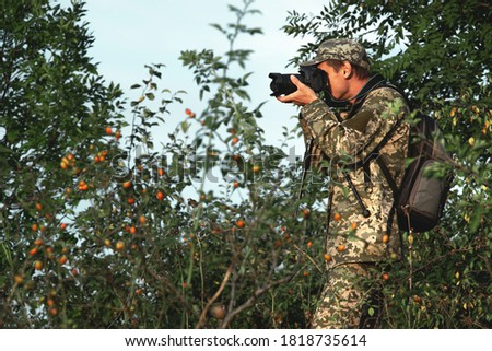 Photographer in camouflage uniform with a camera in his hands and a backpack behind his back
