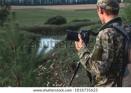 Photographer in camouflage with a camera in his hands on the background of a pond