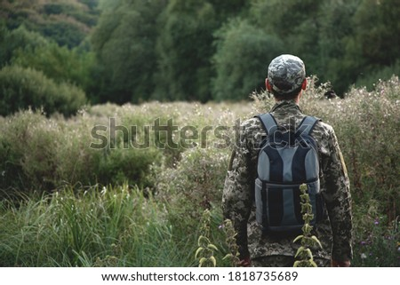 A man in a camouflage uniform with a backpack behind his back stands against the background of the forest
