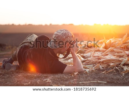 Photographer in camouflage cap takes pictures at sunset