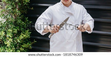 Chef in uniform sharpening a large kitchen knife blade with a steel sharpening stick. Professional equipment preparation before cooking.