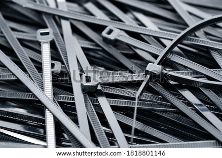 Black Nylon cable ties, hose tie or zip tie background. Flexible nylon tape with an integrated gear rack use for tie and bound cable together  #1818801146