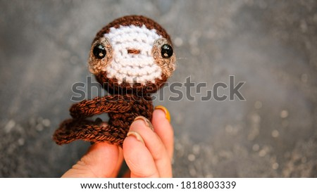 Tiny crochet sloth. Place for text. Dark background. Hand made crochet toy