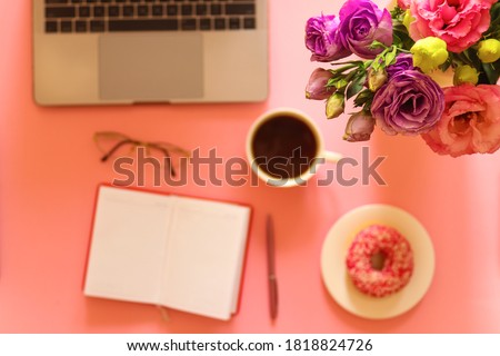 Defocused background with girly workspace with flowers, laptop, donut, coffee notebook, glasses and pen on pink background.Selective focus, blurred. Girly stuff, cute working space.Top view, flat lay.