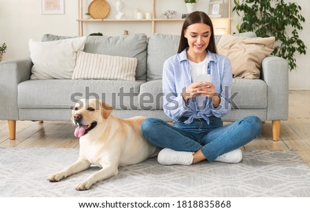 Lifestyle Concept. Portrait of smiling woman using smartphone sitting on the carpet with her purebred dog. Lady spending time at home, chatting at social media, texting sms or reading message Royalty-Free Stock Photo #1818835868