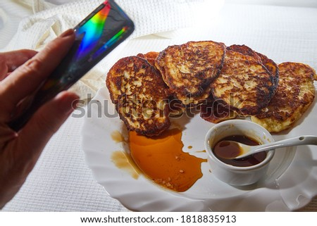 Pancakes on white plate, sweet liquid honey or caramel with a small spoon and taking pictures on cell phone for Instagram. Delicious fried flour food. Unhealthy and harmful, but very tasty food