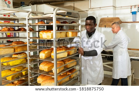 Baker pushing trolley with baked bread. High quality photo