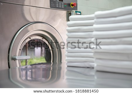 Stack of clean bed sheets in front of industrial washing machine. Focused on washing machines.  Shot taken in the factory. #1818881450