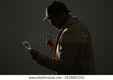 Old fashioned detective with smoking pipe and magnifying glass on dark background Royalty-Free Stock Photo #1818882503