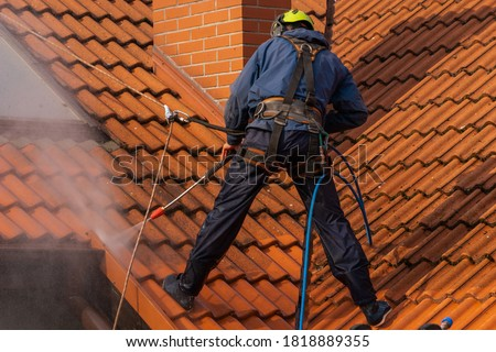 worker washing the roof with pressurized water Royalty-Free Stock Photo #1818889355