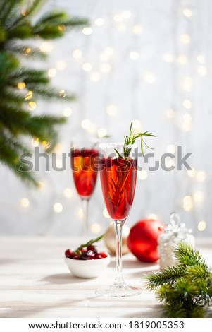 Mimosa festive drink for Christmas - champagne red cocktail Mimosa with cranberry for Christmas party, copy space and fir tree branches vertical photo #1819005353