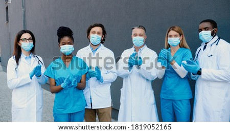Portrait of shot mixed-races young men and women doctors in medical masks, gloves and white gowns standing, applauding and looking at camera. Multi-ethnic medics. Covid-19 victory concept. Applause. Royalty-Free Stock Photo #1819052165