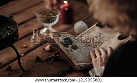 the witch cooks an elixir with herbs in a cauldron, recipe book Royalty-Free Stock Photo #1819055801