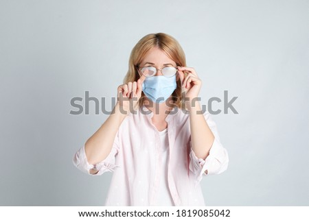 Woman wiping foggy glasses caused by wearing medical mask on light background Royalty-Free Stock Photo #1819085042