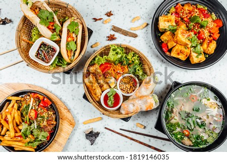 Fresh and delicius Vietnamese food table, Pho ga, pho bowls, noodles, spring rolls, asian dinner table on bright background Royalty-Free Stock Photo #1819146035