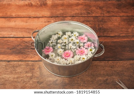 Basin with flowers on wooden background. Digital backdrop for one year old baby photoshoot. Decoration for first birthday. Chamomile, chrysanthemum, gerbera.