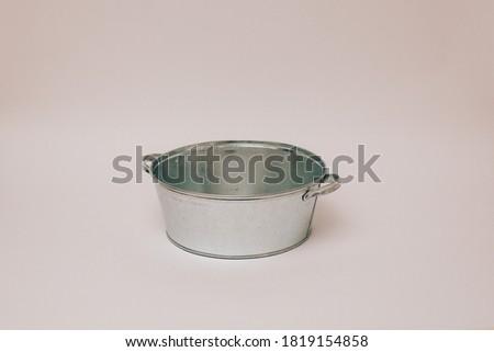 Backdrop for one year old baby photoshoot. Galvanized basin on white background. Washbowl.