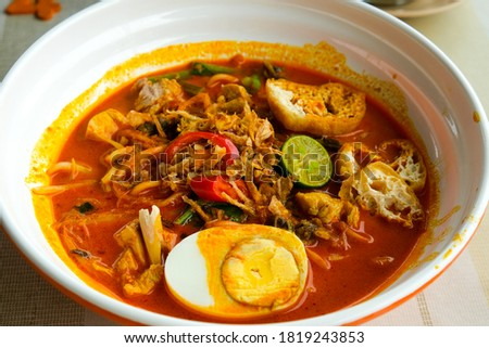 """A closeup picture of Nusantara cuisine called """"curry laksa"""" on the table. Asian dish originated from the Maritime Southeast Asian community particularly in the region of Indonesia and Malaysia."""