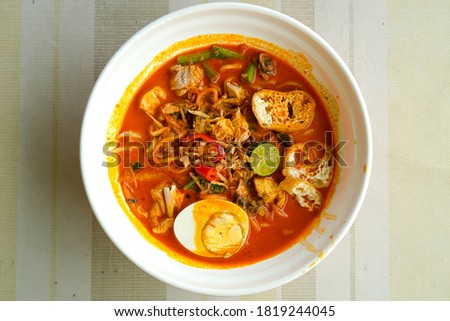 """Flatlay picture of Nusantara cuisine called """"curry laksa"""" on the table. Asian dish originated from the Maritime Southeast Asian community particularly in the region of Indonesia and Malaysia."""