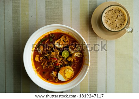 """A flatlay picture of nusantara cuisine called """"curry laksa"""" with milk coffee for breakfast."""