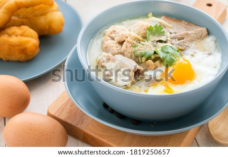 Hot Chinese pork congee top with soft boiled eggs. Pork congee or Chinese Rice Porridge is soft food for patient. Pork congee often served with deep fried dough stick for breakfast. Rice soup concept. #1819250657