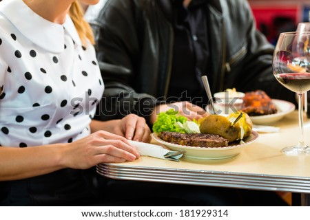 Young couple eating fast food and drinking red wine in a American retro fast food diner #181929314