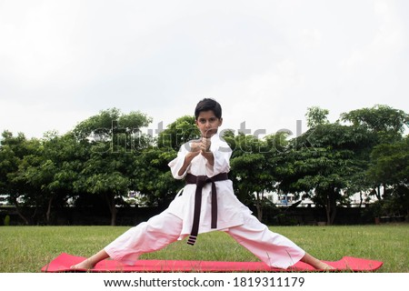 Asian Indian Boy Standing Punching Pose For Martial Arts Practice Wearing White Karategi Taekwondo Uniform Kimono With Green Trees In background #1819311179