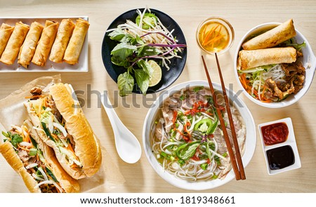 assorted vietnamese dishes with pho, bahn mi, spring rolls in top down composition on dinner table Royalty-Free Stock Photo #1819348661